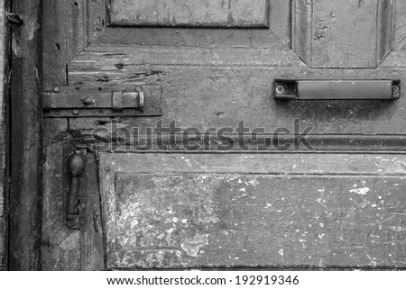 Old, wooden door, wooden and concrete wall and metallic lock - details