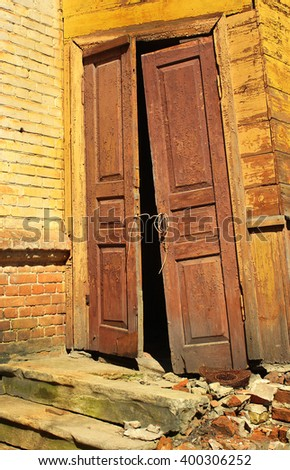 Old wooden doors falling off the hinges - stock photo