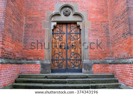 old wooden doors to the red church in Czech republic in Brno with the door knocker and metal ornamental forging, surrounded by the red brick wall and weathered stairs  - stock photo