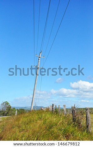 Old wooden electricity post in the countryside - stock photo
