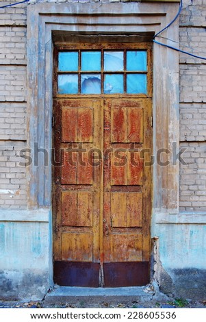 old wooden entrance door with cracked paint - stock photo