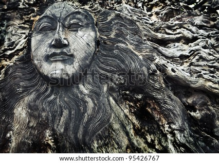 Old wooden face on roots - conceptual background - stock photo