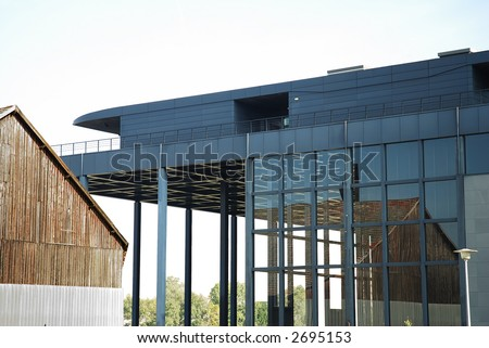 Old wooden factory reflections in a modern Steel and glass building. Concept of architecture contrast - stock photo