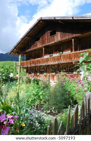 Old wooden farmhouse in the alps with a kitchen garden.