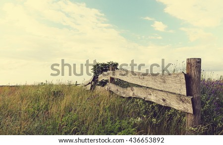 old wooden fence in the beautiful countryside; vintage filter effect - stock photo