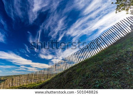 Old wooden fence on dramatic blue sky background