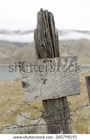 Old wooden fence post with remnants of barbed fencing wire and a rustic empty wood sign with an interesting wood grain pattern - stock photo