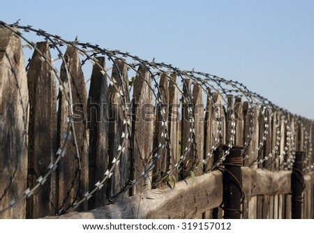 Old wooden fence with barbed wire perspective photo - stock photo