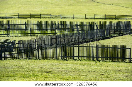 Old wooden fences on green meadow in autumn. Old fences. - stock photo