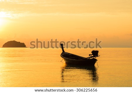 Old wooden fishing boat in sunrise, silhouette, Lipe Island, Thailand.