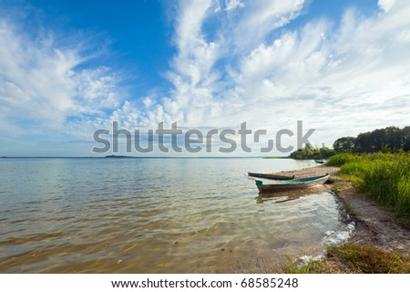 Old wooden fishing boat near the lake shore and summer sky behind (Svityaz, Ukraine) - stock photo