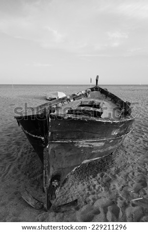 Old wooden fishing boat on the beach and sky up the horison in black and white - stock photo