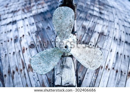 Old wooden fishing boat propeller,artistic toned photo - stock photo