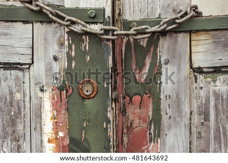 Old wooden gate with rusty chain and aged door lock in Portugal.