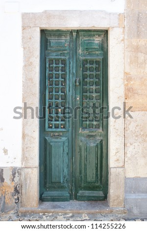 Old wooden green doors on the streets of Portugal. - stock photo