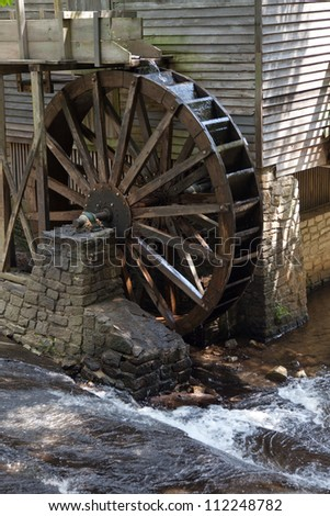 Old wooden, grist mill water wheel, turning with the flow of water - stock photo