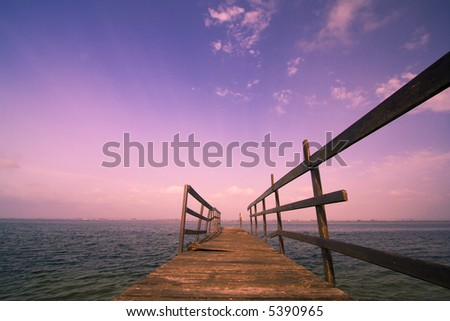 old wooden harbor at sunset - stock photo