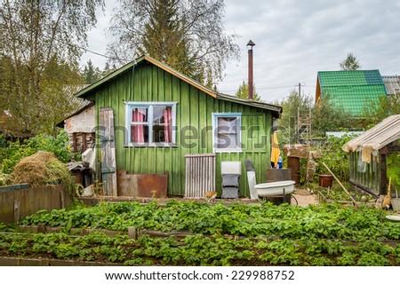 Old wooden house in rural vegetable garden - stock photo