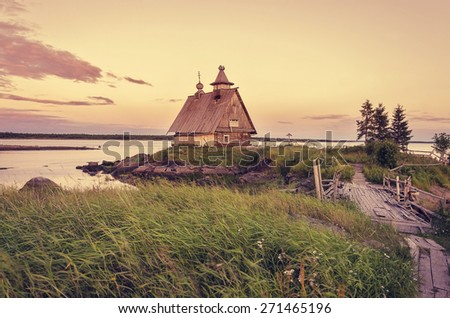 Old wooden house on the beach at sunset. Russia, the White Sea - stock photo