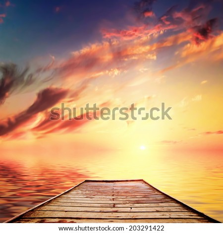 Old wooden jetty, pier on the calm sea. Dramatic sky red clouds. Vintage style - stock photo