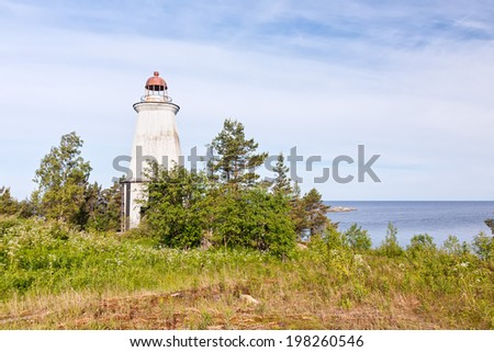 Old wooden lighthouse on Lake Onega granite shore among trees against cloudy sky background. Besov Nos cape, Karelia Republic, Russia