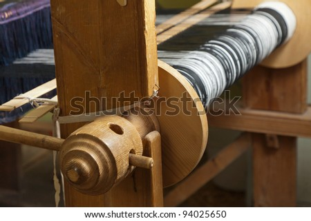 Old wooden loom in weaving - side view. Illuminated by soft light overhead. Close-up - stock photo