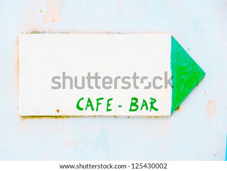 Old wooden made beautiful label showing CAFE-BAR on the wall of a traditional shop in Chora the capital of Amorgos island in Greece - stock photo