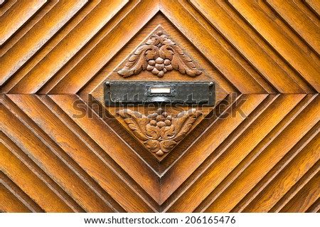 Old wooden mailbox on the door decorated with grape pattern  - stock photo
