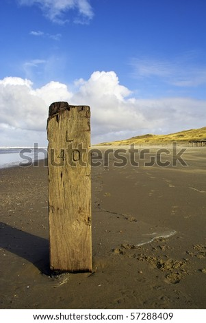 Old wooden marker pole on a beach in Holland - stock photo