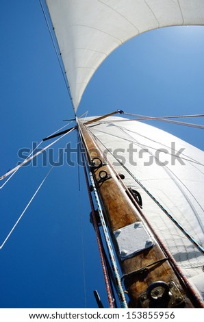 Old wooden mast and white sail, view from deck of boat - stock photo