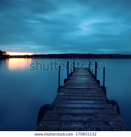 old wooden pier at the lake, sunrise on stormy autumn day - stock photo