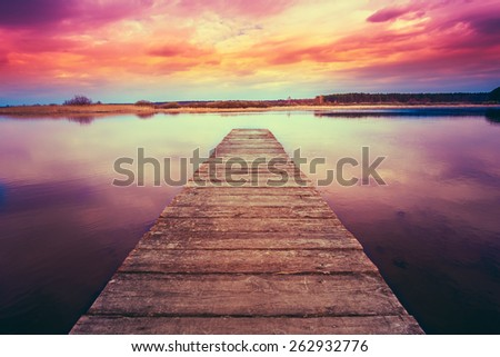 Old Wooden Pier. Calm River Nature Background. Toned Instant Filtered Photo Image - stock photo