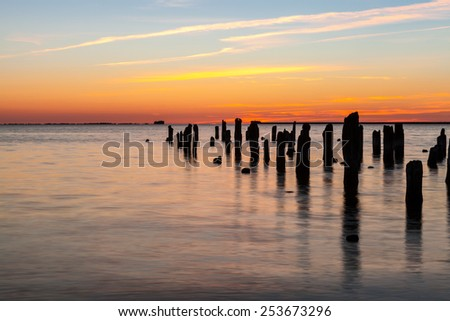 Old wooden pier in harbor at sunset