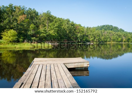 Old wooden pier on small country lake. - stock photo
