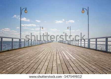 Old wooden pier over the sea shore with copy space - stock photo