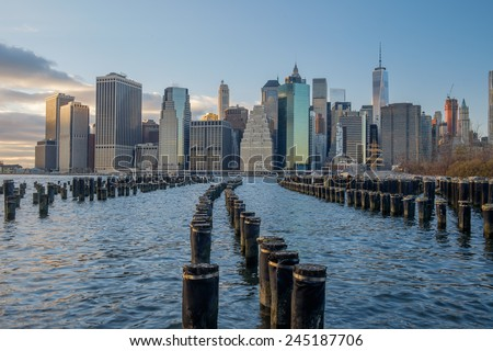 Old Wooden Pilings on the East River reflect the sunset as the lower New York City Manhattan Financial district lights begin to turn on - stock photo