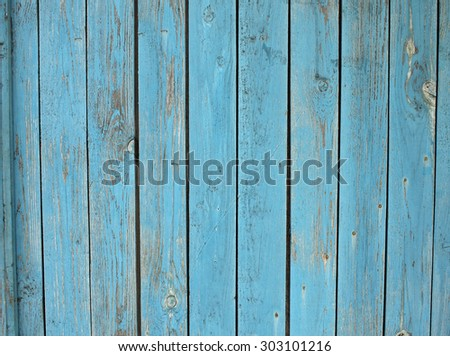 Old wooden planks standing upright with a shabby blue paint all over the field image for use as a background or wallpaper