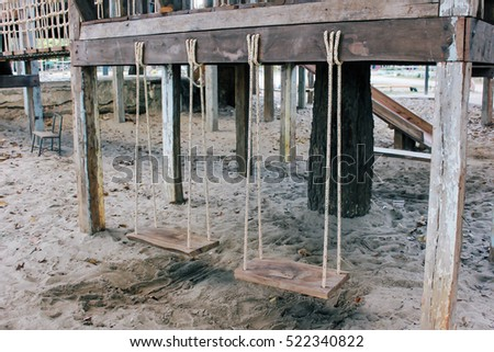 old wooden playground with swings in vintage style.