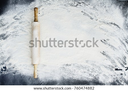 Old wooden rolling pin dusted with white flour over a flour covered dark background. Image shot from above.