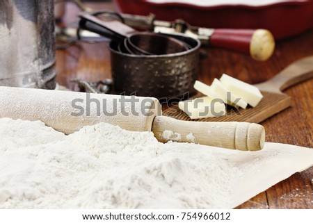 Old wooden rolling pin dusted with white flour over a rustic table. Butter, pie pan and measuring cups in background. Shallow depth of field with selective focus on rolling pin handle.