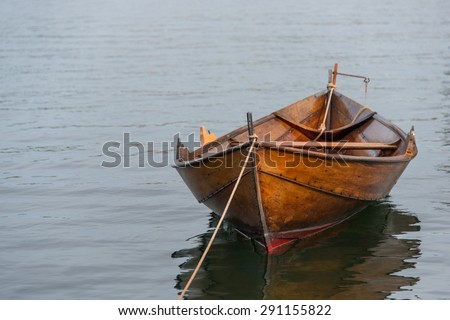 Old wooden row boat moored - stock photo