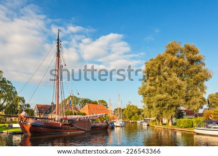 Old wooden sailing boat in a canal in the Dutch village Heeg, Friesland - stock photo