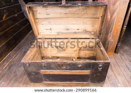 Old wooden sailors trunk with the lid open standing on a wooden deck of an antique sailing vessel, close up high angle view - stock photo