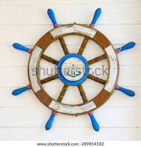 Old wooden ship steering wheel on wood wall. - stock photo