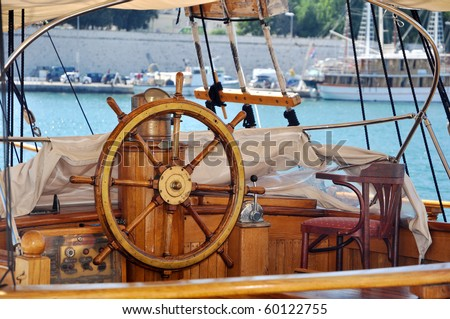 old wooden ship wheel on a yacht, detail photo