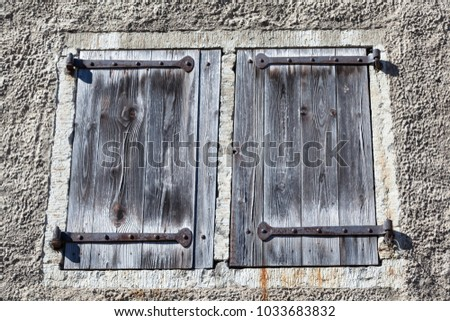 Old wooden shutters with wrought-iron hinges