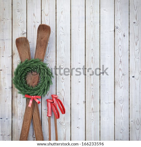 old wooden skis on wooden planks wall with garland and red ribbon, winter background - stock photo