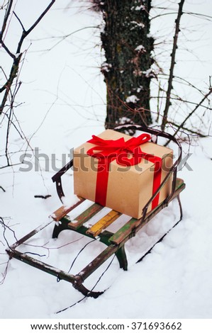 Old wooden sleigh with a gift in golden paper box wrapped red gift ribbon, are in the winter forest, snow, trees near. Wooden sled. Winter and snow. Sled in the snow. A gift from santa. Winter. - stock photo