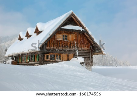 old, wooden, snowy ski lodge in the Alps - stock photo