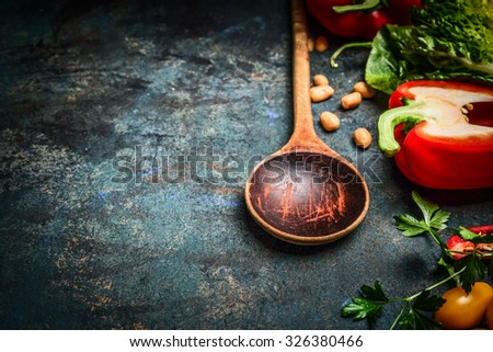 Old wooden spoon and fresh vegetables for tasty vegan cooking on rustic background, close up Healthy food or diet concept. - stock photo